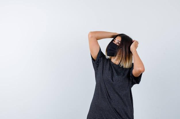 Signora in abito nero, mascherina medica tenendo le mani sulla testa e guardando pensieroso, vista frontale.
