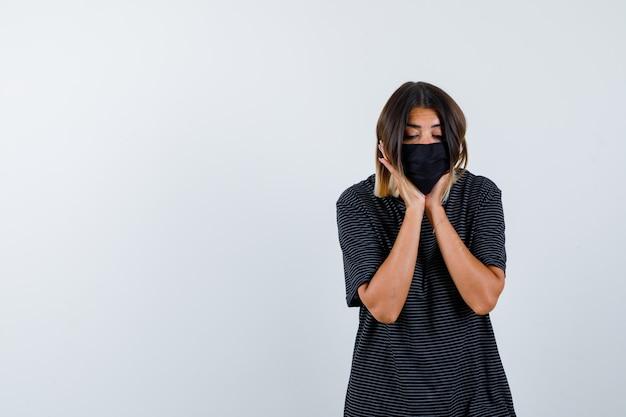 Signora in abito nero, mascherina medica che ricopre la faccia sulle sue mani e sembra pensierosa, vista frontale.