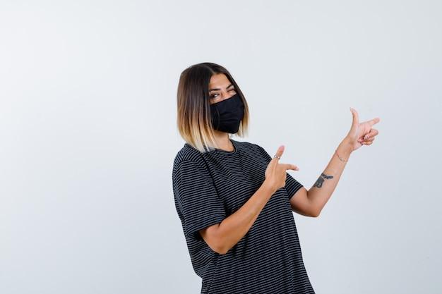 Signora in abito nero, maschera medica che punta a destra e sembra sicura, vista frontale.