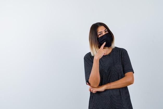 Signora in abito nero, mascherina medica che punta all'angolo in alto a destra e che sembra esitante, vista frontale.