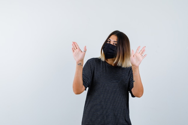 Signora in abito nero, mascherina medica che mostra il gesto di arresto e guardando attento, vista frontale.