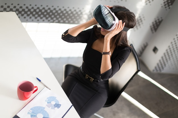 Lady in black strong suite sit at the office table in vr glasses