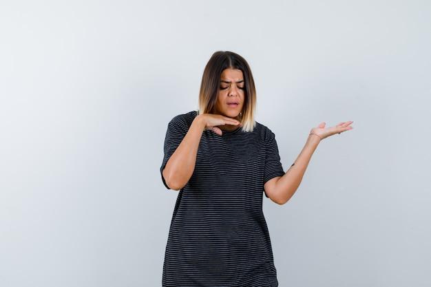 Signora in maglietta nera che tiene la mano sotto il mento, allargando il palmo da parte e guardando pensierosa, vista frontale.