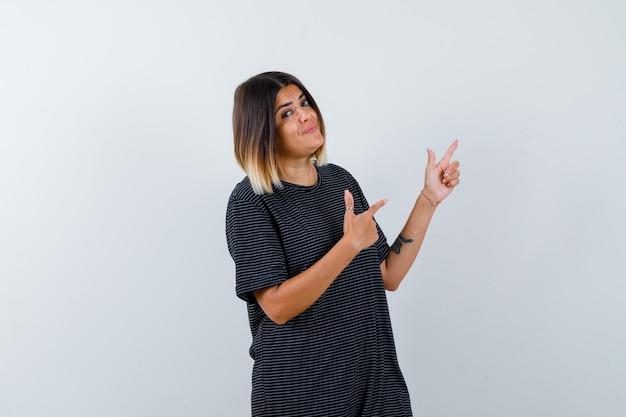 Signora in maglietta nera che punta all'angolo in alto a destra e sembra allegra, vista frontale.
