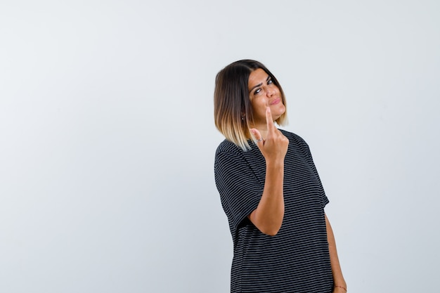 Lady in black t-shirt showing one finger and looking jolly , front view.