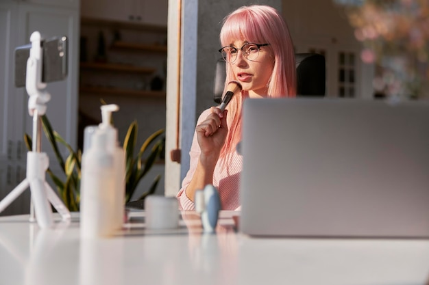 化粧品とラップトップを備えたテーブルでの女性ブロガーの新しい化粧ブラシ撮影チュートリアル