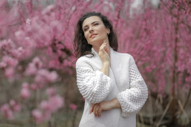 Lady in blooming bushes. woman in white sweater and skirt.