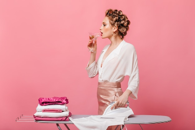 Lady in blouse and silk skirt drinks martini and ironing clothes