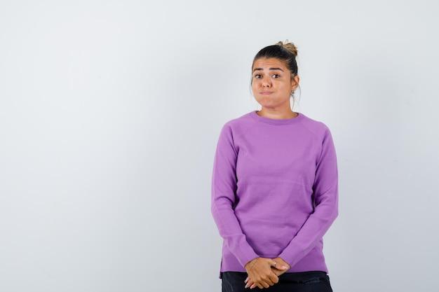 Signora che soffia sulle guance mentre guarda la telecamera con una camicetta di lana e sembra confusa