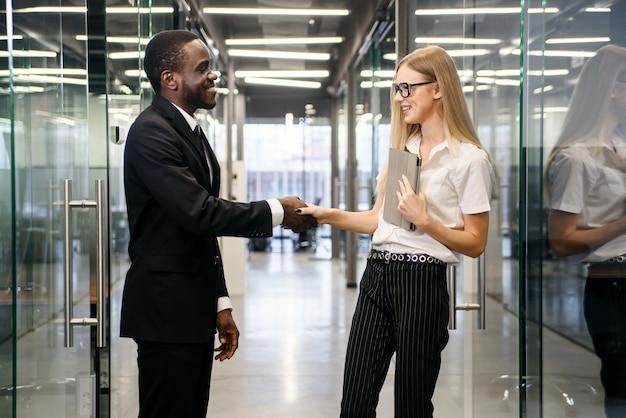 お互いに挨拶する新しいアフリカの従業員と女性の上司のハンドシェイク。会議を開始して握手するオフィスの廊下を歩いて多民族のビジネス部門の同僚。