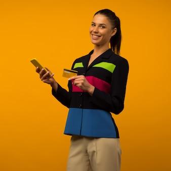 노란색 배경에 신용 카드와 스마트 폰으로 온라인 구매 레이디