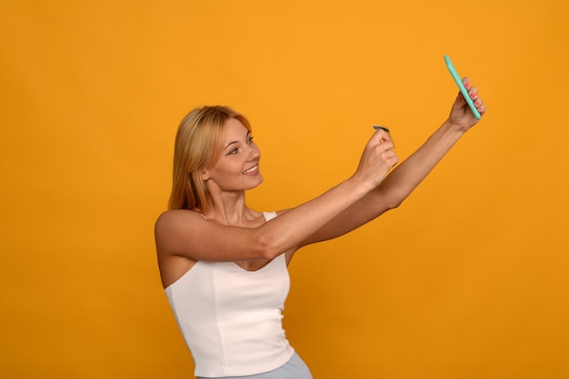 黄色の背景にクレジットカードとスマートフォンでオンラインで購入する女性