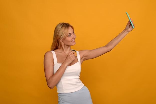 黄色のクレジットカードとスマートフォンでオンラインで購入する女性
