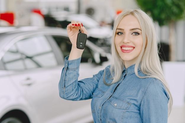Signora in un salone di automobile. donna che compra l'auto. donna elegante in un vestito blu.
