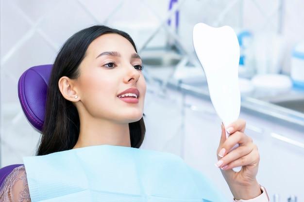 女性は鏡で彼女の歯をチェックします。