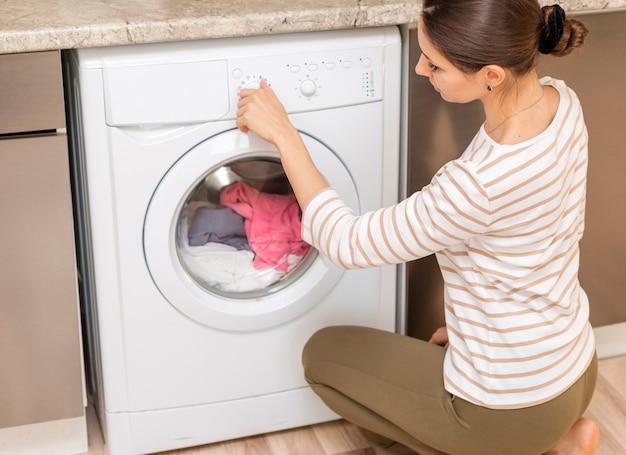 Lady choosing program on washing machine