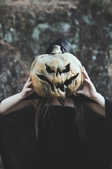 Lady closing face by gloomy pumpkin in park
