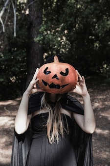 Lady closing face by pumpkin in park