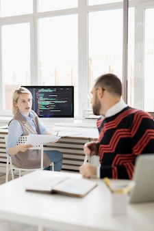 Lady coder giving information about app to colleague