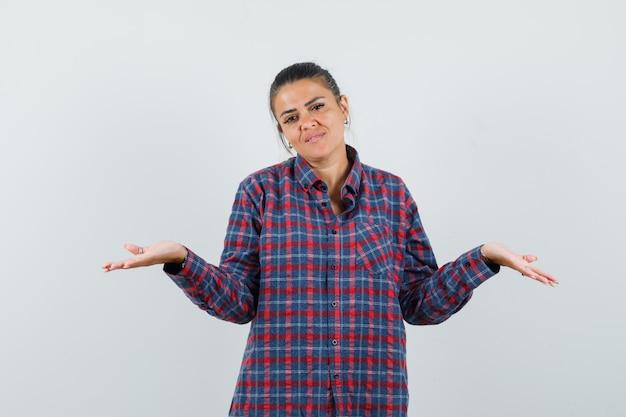 カジュアルなシャツで何かを比較または提示し、自信を持って見える女性。正面図。