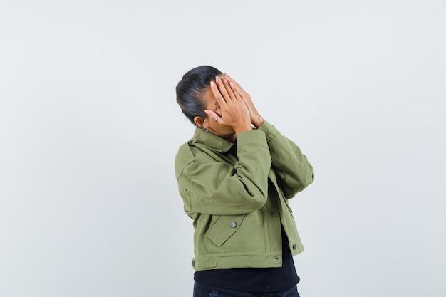 ジャケットの手で顔を覆う女性