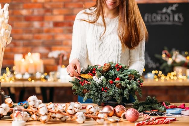 오렌지 슬라이스 녹색 전나무 트리 크리스마스 화 환을 장식하는 아가씨.