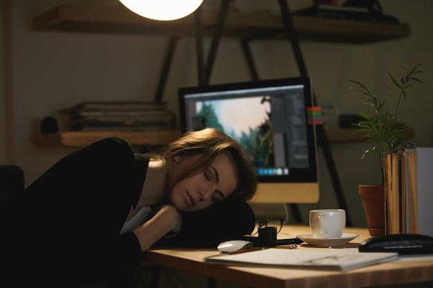 Lady designer sleeping on workspace
