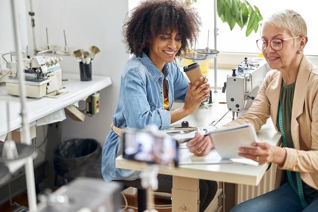女性の洋裁は、スタジオでアフリカ系アメリカ人の同僚にスケッチブックで新しい服のモデルを示しています