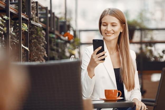 Леди пьет кофе. женщина, сидящая за столом. девушка пользуется телефоном.