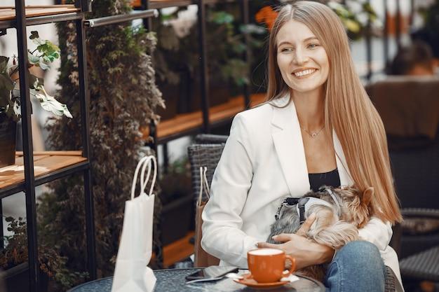 레이디는 커피를 마신다. 테이블에 앉아 여자입니다. 귀여운 강아지와 소녀입니다.