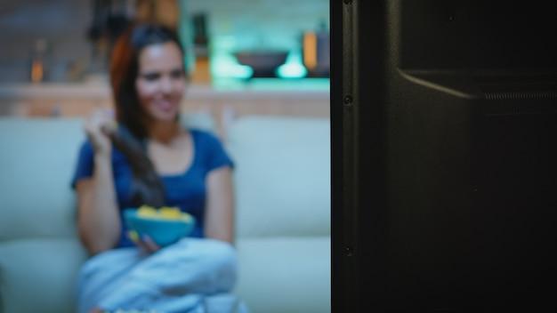 소파에 앉아 tv를 보면서 간식을 먹는 아가씨. 젊고 행복하고 신나고 즐겁게 잠옷 차림으로 집에 혼자 있는 여성이 텔레비전 앞에서 팝콘을 먹고 있는 편안한 소파에 앉아 저녁을 즐기고 있습니다.