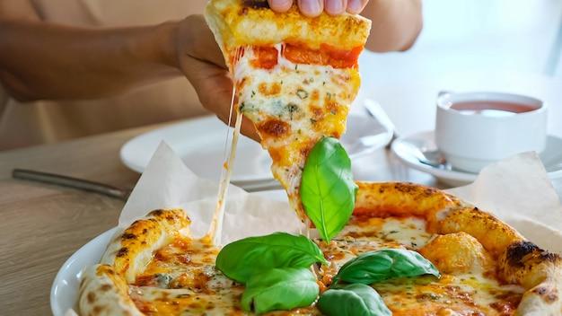 女性はピザを食べます。若い女性の手はおいしいスナックスライスを取り、カフェの超クローズビューの茶色の木製テーブルのティーカップの近くに白いプレートを置きます
