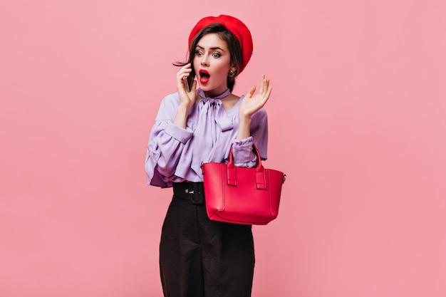 Signora in vestiti eleganti e cappello rosso che tiene borsetta e parla al telefono con sorpresa.