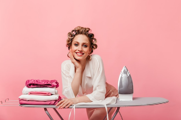 Lady in elegant outfit with smile looks at front and leans on ironing board