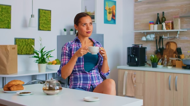 Lady enjoying a hot green tea sipping from porcelain cup. woman drinking standing at the table in the kitchen and looking through the glass holding tea cup with natural, aromatic herbal drink.