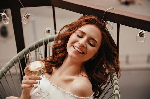 女性は白ワインを楽しみ、バルコニーに座っています