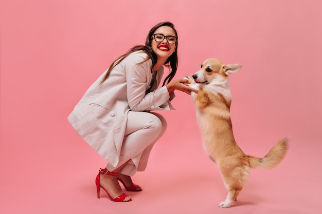 Lady in eyeglasses and suit plays with corgi on pink background.  happy woman in office attire and red high heels smiles and holds corgi.
