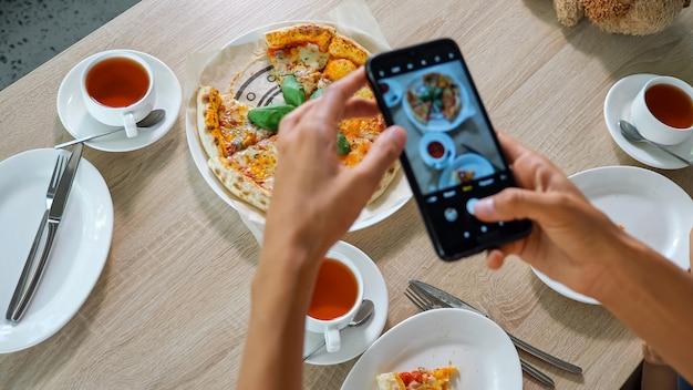 女性は食べ物を撮影します。若い女性は現代的な黒のスマートフォンを持って、木製のカフェテーブルでおいしいピザとお茶の写真を間近で見る