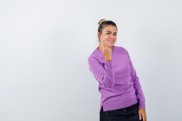 Дама жестикулирует рукой и пальцами в шерстяной блузке и выглядит весело