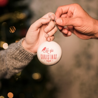 Lady giving to guy decorative Christmas ball