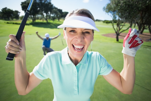 Lady golfer cheering at camera with partner behind