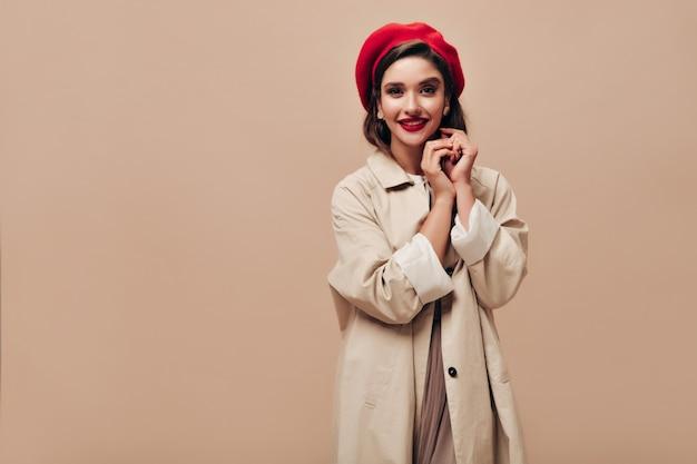 Signora di buon umore esamina la macchina fotografica su sfondo beige. bella donna sorridente con grandi labbra luminose in berretto rosso, in orecchini e in posa cappotto lungo.