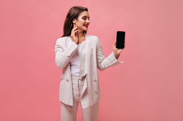 Lady in great mood holds smartphone on pink background.  cute business woman in beige office suit looks at phone on isolated backdrop.