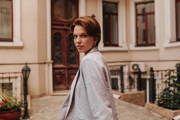 Signora in giacca grigia esamina la macchina fotografica sullo sfondo dell'edificio. una donna dai capelli corti in abito oversize cammina fuori