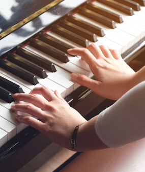 Lady hand is playing piano for music