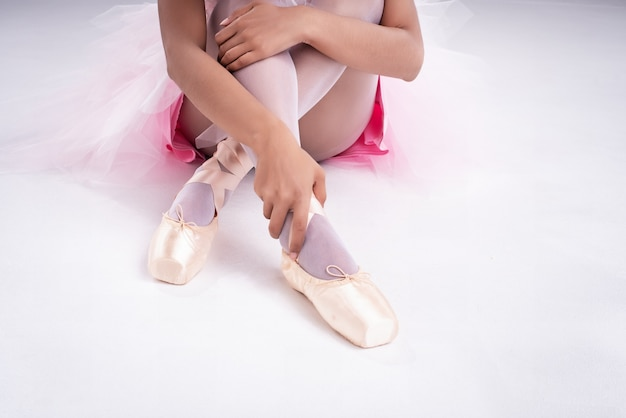 The lady hand is touching satin ballet shoe with right hand,