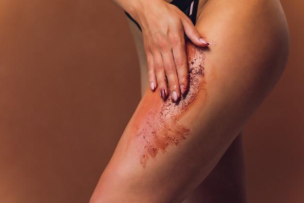 Женская рука на крем для смазывания ног показывает хороший результат в бледно-розовом бюстгальтере.
