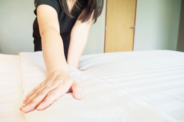 Lady hands set up white bed sheet in hotel room