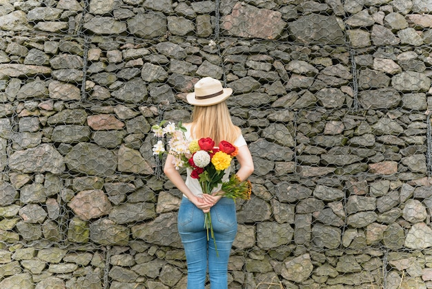 Lady in hat with bouquet of flowers from back near wall