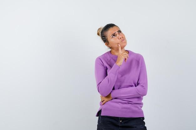 ウールのブラウスで顎に指を持って物思いにふける女性